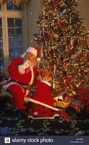 santa claus puts toys under christmas tree shhhh stock photo