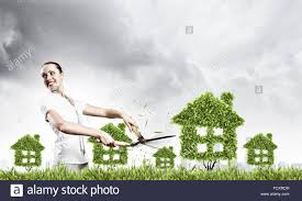 young attractive businesswoman cutting lawn in shape of house
