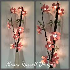 decorating lighted branches with paper flowers for wall