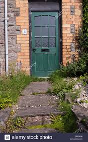 green front door to house with number 4 and overgrown stone path