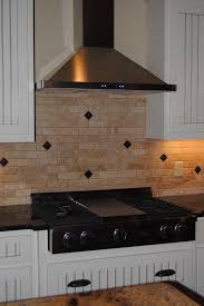 white wooden kitchen cabinet and stone tile ornament fleur de lis kitchen decor also small cooktop plus black granite countertop