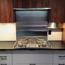 miele gas cook top with stainless steel backsplash and hood