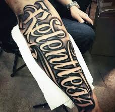 mens relentless script on outer forearm with neagtive space