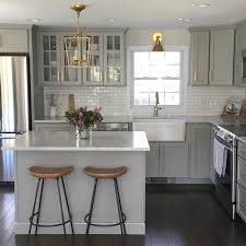 gray kitchen features gray shaker cabinets adorned with brass