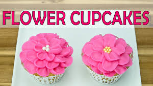 piping buttercream icing flowers on cupcakes by cookies cupcakes