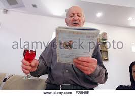 transliterated haggadah reading the haggadah around a table set for a festive meal