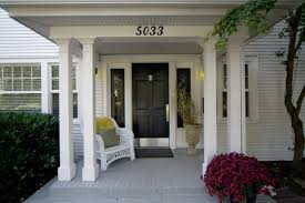 this classic front entrance features a covered front porch with a