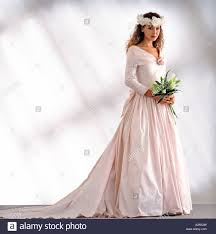 pretty young bride stands ready in a pale pink wedding dress