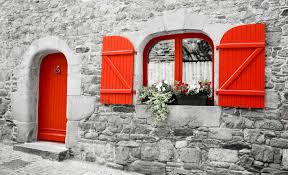 old stone house with red wooden shutters and red door 277693430