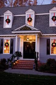 christmas lights in windows wreaths hanging by a red ribbon on each window holiday decor