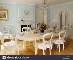 painted cream table and chairs with white cushions in traditional