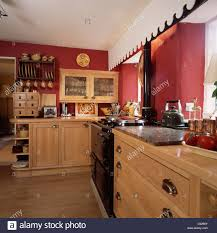 black aga and pale wood fitted units in red country kitchen stock