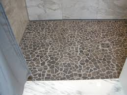 copious recycled grey pebble shower floor with white marble wall