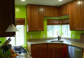 bright green kitchen wall with wooden cabinets and blinds for