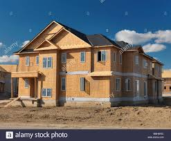 wooden frame two story house with osb sheathed walls under stock