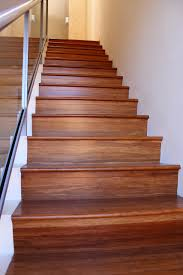 vinyl wood plank flooring on stairs with glass railings and
