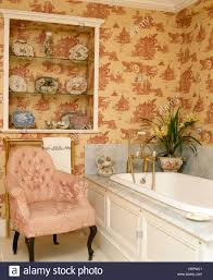 Button Back Armchair Pink Toile De Jouy Wallpaper And Simple White Shelves In Bathroom