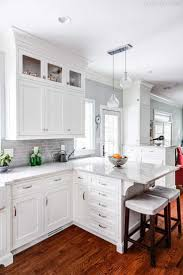 white kitchen cabinets with gray quartz countertops brown