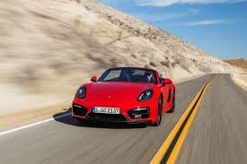 driving a porsche boxster 2015 porsche boxster gts in guards color driving front