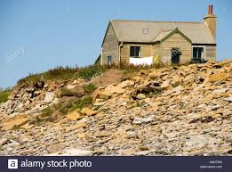 small beach house on the cliffs in orkney scotland stock photo