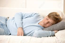 tired young man sleeping on couch taking afternoon nap stock