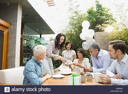 woman serving cake to friends at outdoor dinner party stock photo