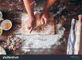 hands kneading raw dough on table stock photo 563023327 shutterstock