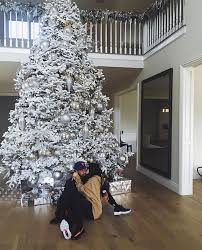 kylie jenner and tyga cuddle in front of the christmas tree in