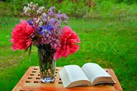 Flowers In A Book - table bouquet of summer flowers and a book in a garden stock