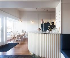petone restaurant comes and goes has soft design and bold food a curved counter with white timber battens curves from the kitchen past no 18 bentwood bar stools by thonet and a slim wall mounted oak leaner