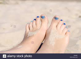closeup on woman sandy feet with blue nails pedicure under