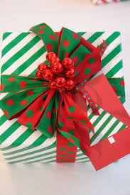 festive green and white gift wrap with fun berry and bows topper