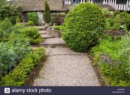 gravel pathway through kitchen garden borders leading to the house
