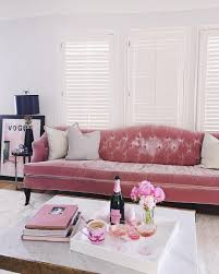 pink and gold living room features a pink curved velvet sofa lined