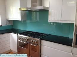 turquoise coloured glass splashback in a white kitchen with dark