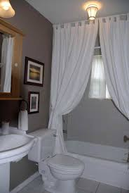 white curtain room dividers with white bathtub and closet for