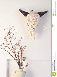 cow bull head and dried berry flowers home decor on white wall