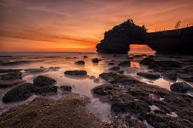 Sunset Orange by Orange And Yellow Sunset Skies Over Grey Seashore Rocks And Calmed