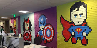 best coworkers ever create superhero murals with post it notes screengrab of a time lapse video of people building superhero post it note murals