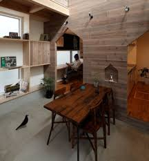 hazukashi house with wooden double height dining room and timber