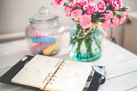 Flowers On - personal organizer and pink flowers on desk free stock photo