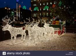 sleigh pulled by reindeer made from lights the focus of the