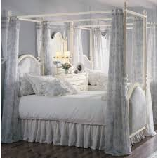 bedroom bed with thick bedding and high canopy bedframe