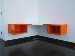 curved orange stained wooden floating shelf with cubicle storage