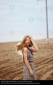 beautiful in dress with hat on spring field a royalty free
