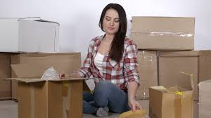 woman uses adhesive tape dispenser packing cardboard boxes for