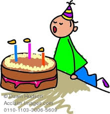 image of a little boy blowing out candles on his birthday cake