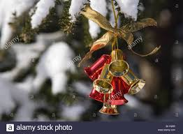 jingle bells ornament hanging outside on tree in snow