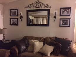 behind couch wall in living room mirror frame sconces and metal