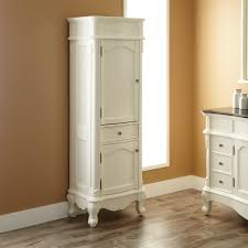 bathroom tall white wood cabinet with glass door and drawers for